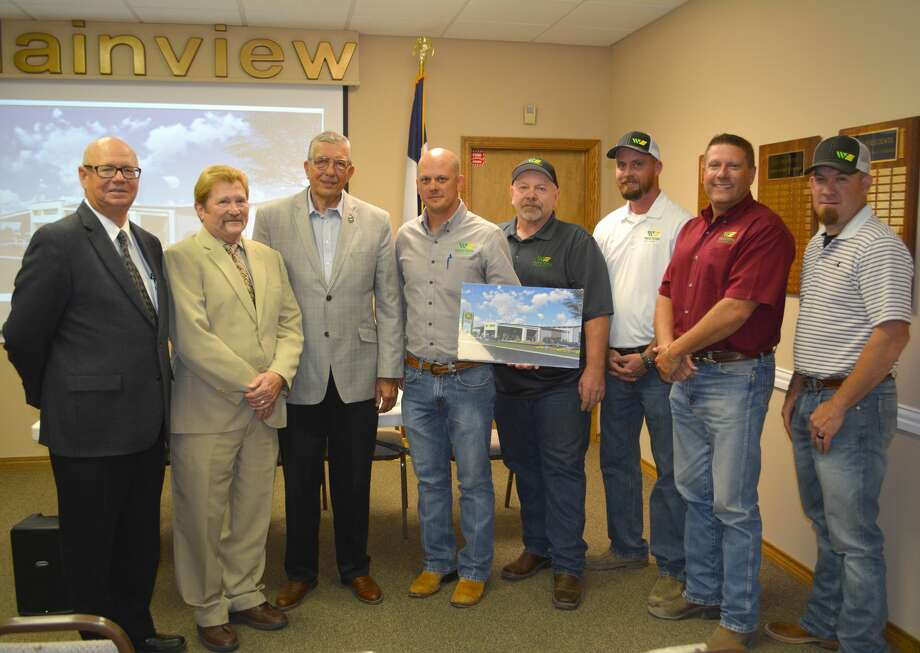 Colby Flaming, co-owner of Western Equipment, displays a photo of the John Deere dealership's new facility which will become the first tenant of the new Plainview-Hale County Business Park. On hand for the announcement Tuesday are Plainview-Hale County Economic Development Executive Director Mike Fox (left), Hale County Judge Bill Coleman, Plainview Mayor Wendell Dunlap, Flaming, and local Western Equipment representatives Travis Morgan, parts manager; David Fisher, service manager; David Drake, store manager; and Isaac Richardson, construction manager Photo: Doug McDonough/Plainview Herald
