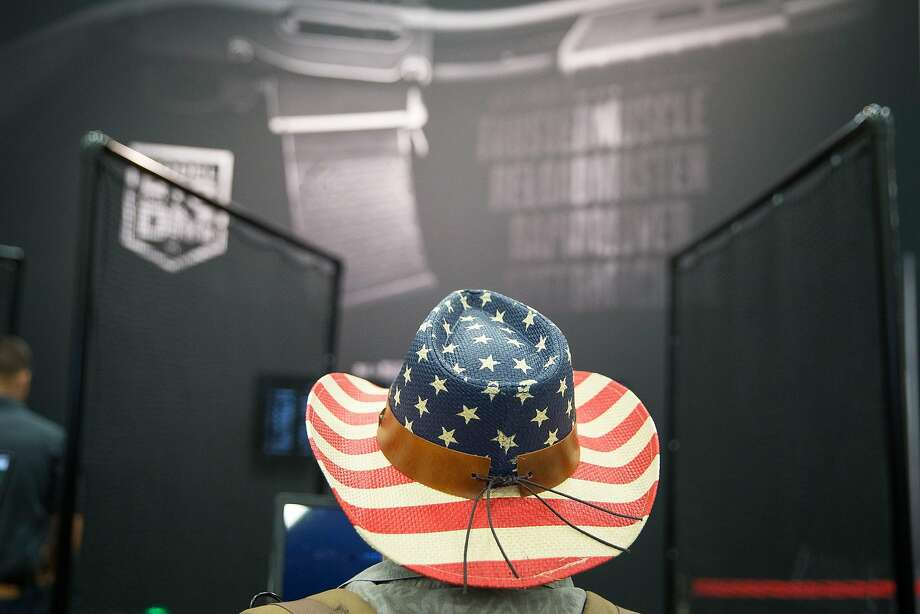 A man in an American flag hat walks through an exhibit hall at the National Rifle Association's convention in Dallas on Saturday. Photo: LOREN ELLIOTT;Loren Elliott / AFP / Getty Images