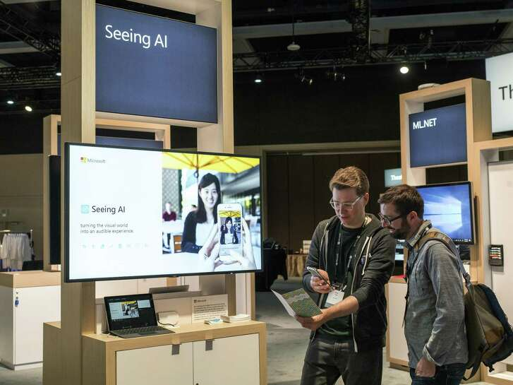People examine the Seeing AI app, which helps blind people in everyday life, during Build, a three-day conference for developers in Seattle, May 7, 2018. More than 100 business leaders — in sectors ranging from energy and manufacturing to health care, technology and financial services — senior government officials and experts will convene in Washington for a summit to address issues around AI.