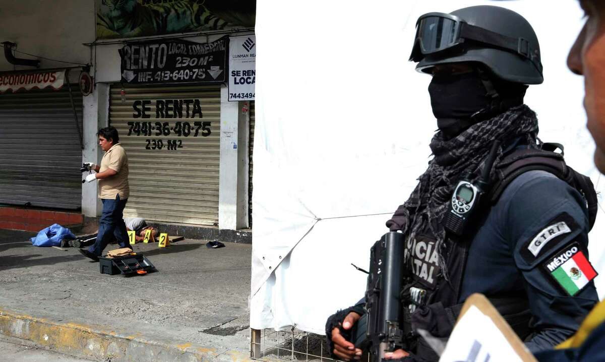 A police officer tapes off the area where an auxiliary police officer lies dead after confronting assailants at the strip mall he was guarding in Acapulco, Mexico, Tuesday, July 31, 2018. Mexico's National Statistics Institute, INEGI, reports that the homicide rate in 2017 broke down to 25 per 100,000 inhabitants. (AP Photo/Bernandino Hernandez)
