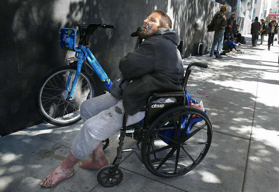 A man in a wheelchair not far from heroin users on Mission near Eighth streets. City Hall has taken decisive action on scooters plaguing  sidewalks but has done little on the homeless, drug use and problems with garbage and human waste. Photo: Liz Hafalia / The Chronicle