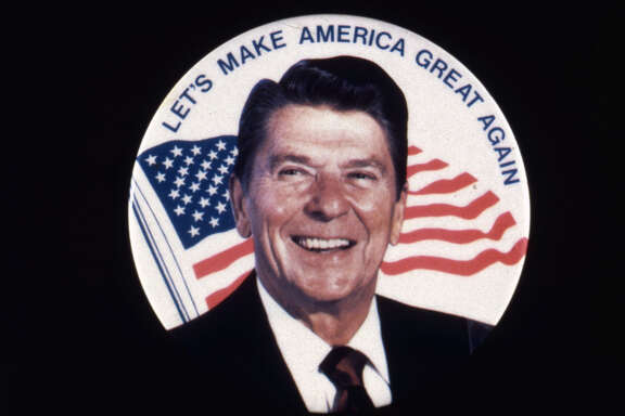 Ronald Wilson Reagan, the 40th president of the United States. A former actor and president of the Screen Actors Guild, he was elected governor of California in 1966 and US president in 1981. He is standing in front of a sign reading 'Let's Make America Great Again', during his electoral campaign. (Photo by MPI/Getty Images)