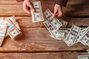 Male hands counting dollars. Cash on brown wooden background. All you have earned. Good reward for a businessman.