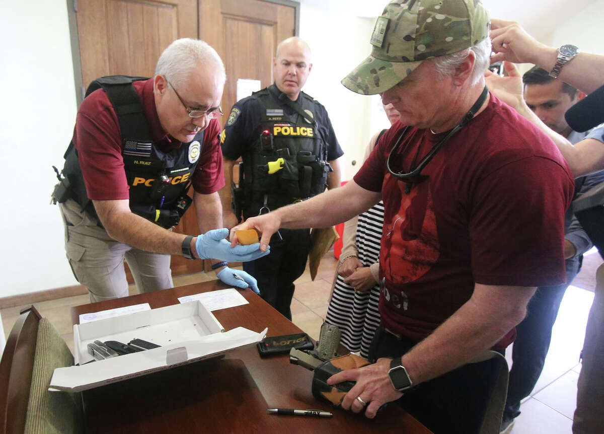 CJ Grisham, (right, wearing cap) the founder of Open Carry Texas, picks up belongings Wednesday May 9, 2018 from Olmos Park police. The items were taken by the police department when Grisham was arrested last March after a gun rights demonstration. The man on the left was wearing a name tag identifying him as H. Ruiz and the man in the center was wearing a name tag identifying him as A. Reed. Niether would release their first name. All charges against Grisham have been dropped.
