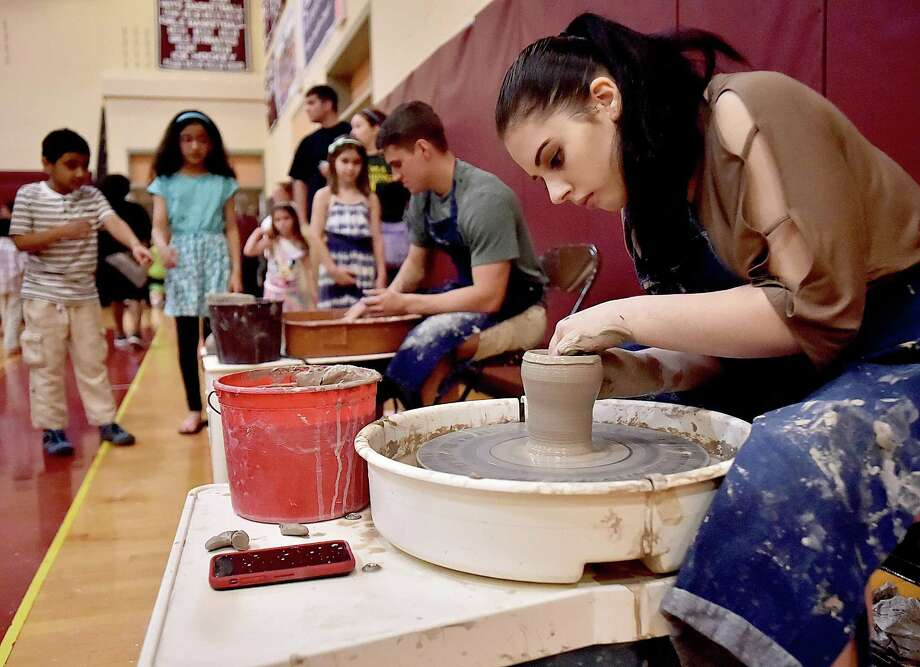Sierra Kusmit, a senior in the ceramic design class and Jacke Bencivengo, a senior art student make bowls using pottery wheels at Art Beat at the North Haven Public Schools Art Celebration, Thursday, May 3, 2018, at North Haven High School. Kusmit proposed the idea of a live demonstration to her ceramic teacher at last year's Art Beat when she noticed young students' interest in the pottery wheel on display. Photo: Catherine Avalone / Hearst Connecticut Media / New Haven Register