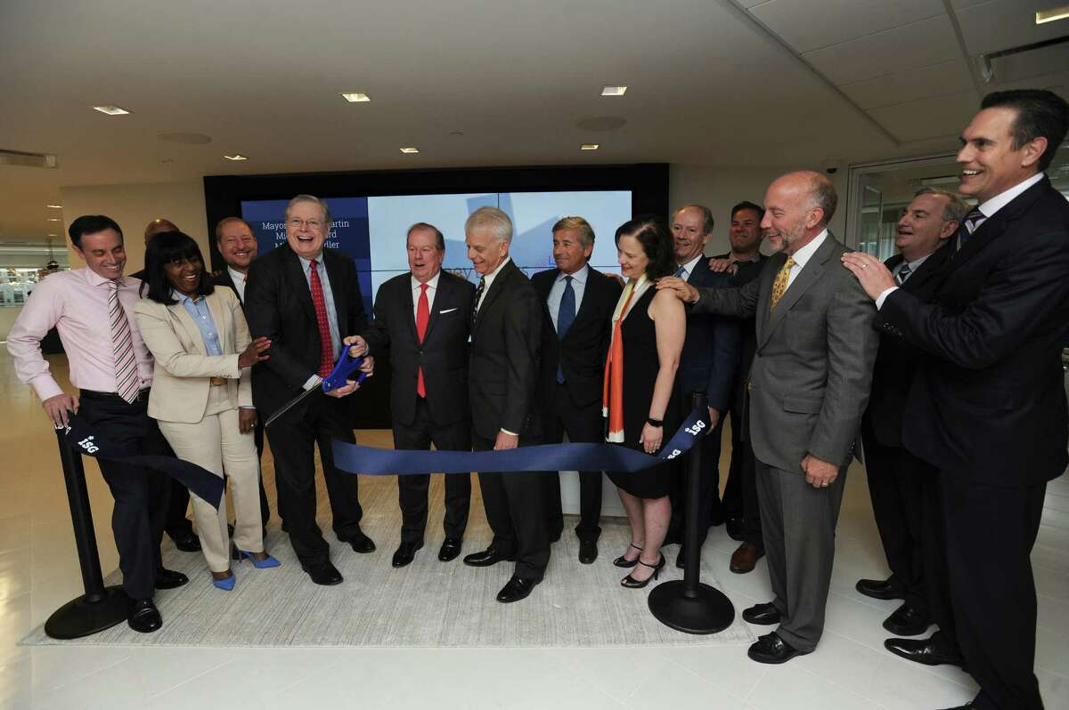 Stamford mayor David Martin (center left) and ISG CEO Michael Connors cut the ceremonial ribbon at the IT consulting and research firm's new offices on Atlantic St. in the Harbor Point area of Stamford, Conn. on Wednesday, May 9, 2018.