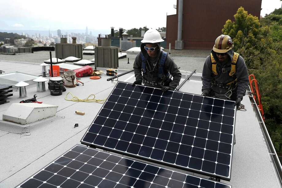 Luminalt solar installers Pam Quan (L) and Walter Morales (R) install solar panels on the roof of a home on May 9, 2018 in San Francisco, California. The California Energy Commission approved legislation that requires all new homes in the state of California to have solar panels. The new mandate would require the panels on new homes up to three stories tall and is estimated to cost nearly $10K per home. Photo: Justin Sullivan /Getty Images / 2018 Getty Images