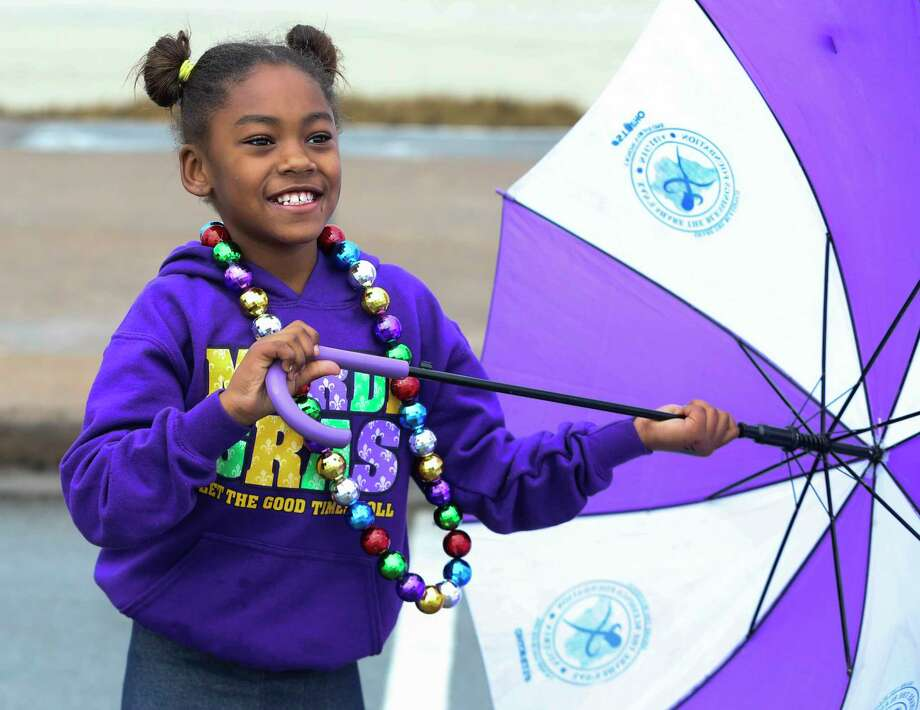 Unique Burnom, 8 years old of Dallas, plays with an umbreslla as it is drizzling to watch the Krewe d'Esprit Rosaire Parade on Seawall Boulevard on Saturday, Feb. 10, 2018, in Galveston. ( Yi-Chin Lee / Houston Chronicle ) Photo: Yi-Chin Lee, Houston Chronicle / © 2018  Houston Chronicle