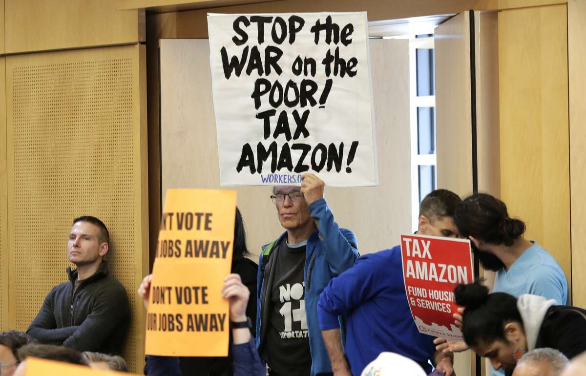 Jim McMahan, of Seattle, holds a sign that reads