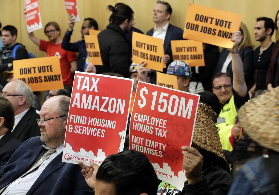 Opponents and supporters of a controversial proposal to tax large businesses such as Amazon.com to fund efforts to combat homelessness hold signs Wednesday, May 9, 2018, as they attend a Seattle City Council committee meeting at City Hall in Seattle. (AP Photo/Ted S. Warren) Photo: Ted S. Warren/AP