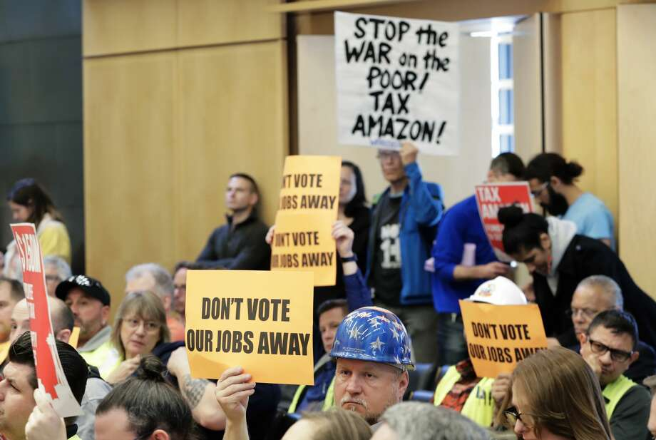 "Jimmy Haun, center, holds a sign that reads ""Don't vote our jobs away,"" Wednesday, May 9, 2018, as he attends a Seattle City Council committee meeting at City Hall in Seattle where public comment was heard on a controversial proposal to tax large businesses such as Amazon.com to fund efforts to combat homelessness. Haun is the political director of the Pacific Northwest Regional Council of Carpenters. (AP Photo/Ted S. Warren) Photo: Ted S. Warren/AP"