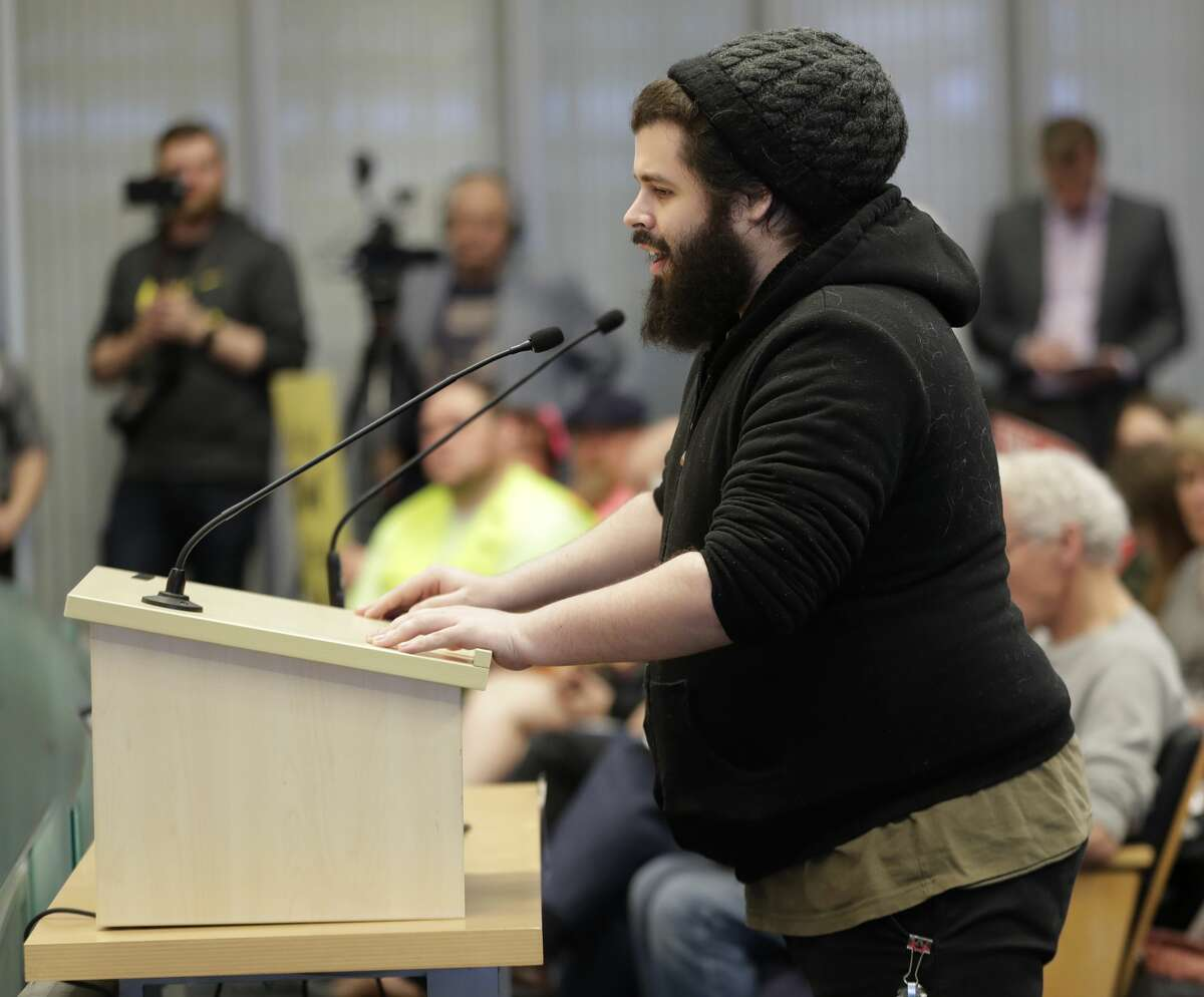 Vince Lach, a case manager with the Downtown Emergency Service Center, which provides services to homeless people in Seattle, speaks in favor of a controversial proposal to tax large businesses such as Amazon.com to fund efforts to combat homelessness, Wednesday, May 9, 2018, during a Seattle City Council committee meeting at City Hall in Seattle. (AP Photo/Ted S. Warren)