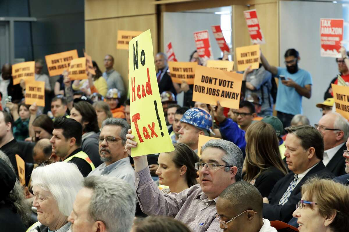 Opponents and supporters of a controversial proposal to tax large businesses such as Amazon.com to fund efforts to combat homelessness hold signs Wednesday, May 9, 2018, as they attend a Seattle City Council committee meeting at City Hall in Seattle. (AP Photo/Ted S. Warren)