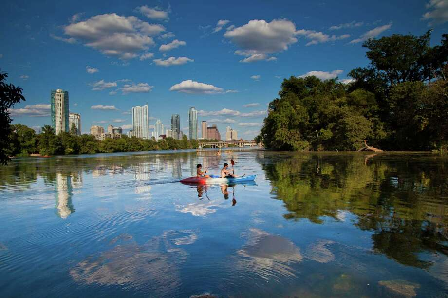 Kayakers take in the Austin skyline from Lady Bird Lake, which is encircled by a hiking-and-biking trail that stretches more than 10 miles. Photo: Austin Convention & Visitors Bureau / Austin Convention & Visitors Bureau
