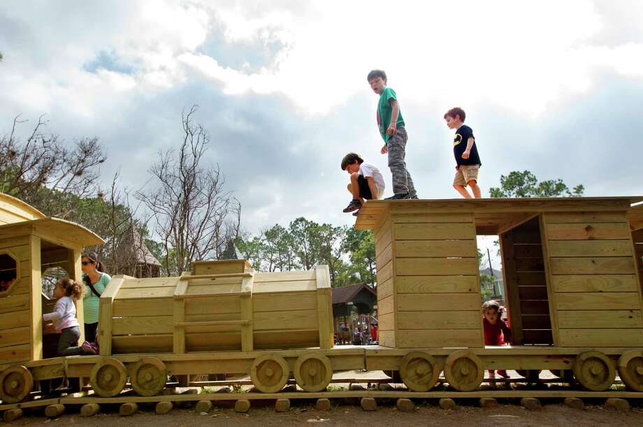 "Fisher McFarland, 6, top center left, Asher Robinson, 7, top center, and Bradley Joe Collins, 5, top center right, play on a wooden train at Donovan Park, Monday, Feb. 17, 2014, in Houston. ""It's so beautiful,"" Dana Robinson Asher's mom said. ""I love Houston weather."" (Cody Duty / Houston Chronicle) Photo: Cody Duty, Staff / © 2014 Houston Chronicle"