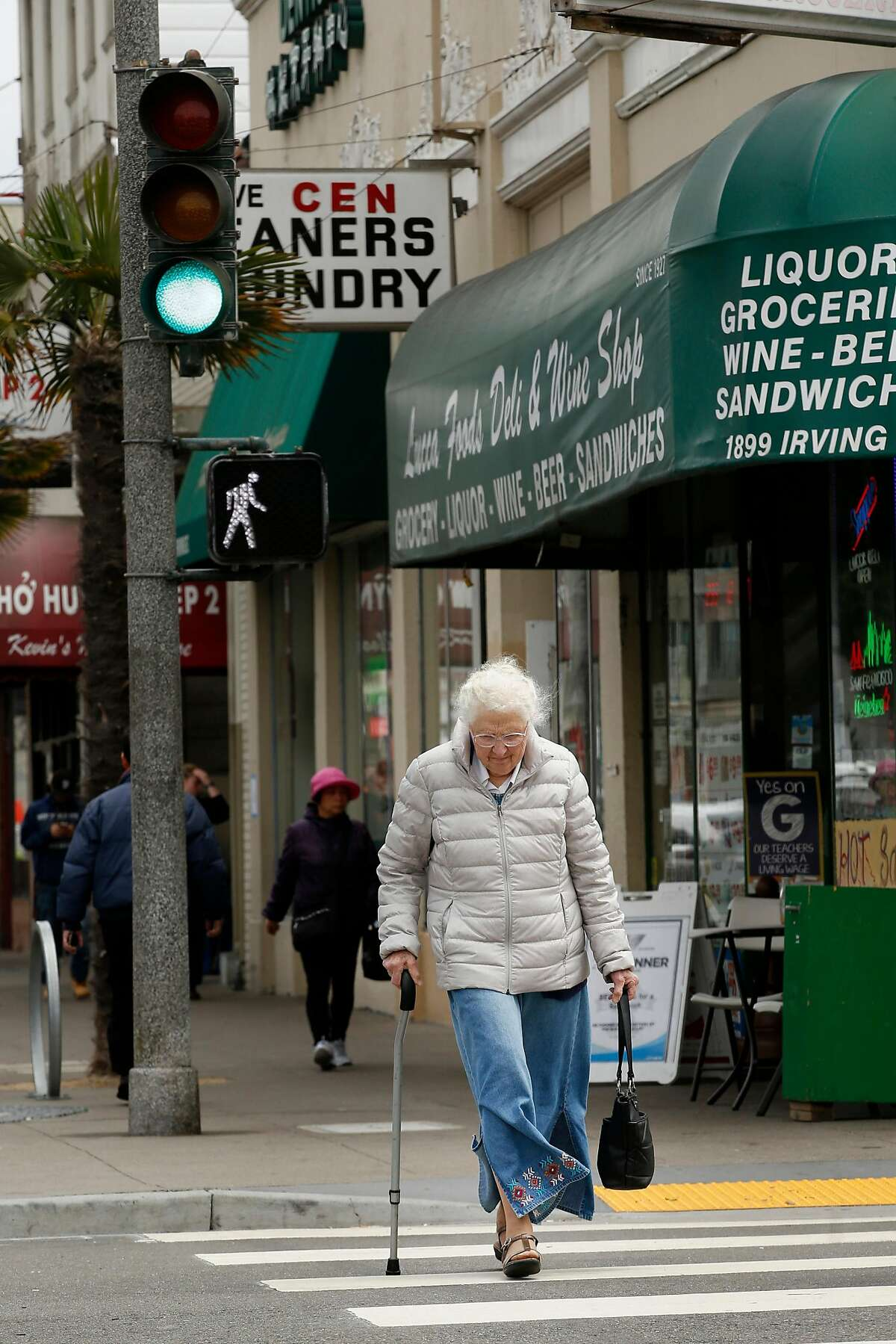 """Valerie Meehan, age 93, makes her way down the crosswalk at Irving Street, Tuesday, May 8, 2018, in San Francisco, Calif. The Municipal Transportation Agency agreed to give people more time to get across the street in busy intersections by slowing the signal timing from 3 feet per second to 4.5 feet per second. Meehan, a native San Franciscan, said the time extension would be very helpful. """"If I don't start immediately it's hard to get across and I have difficulty breathing when I have to walk fast,"""" Meehan said."""