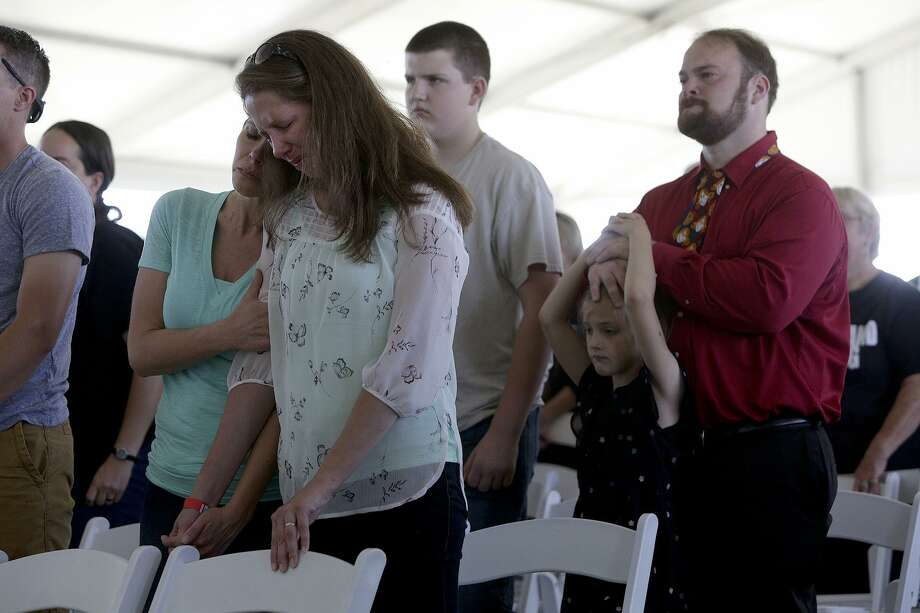 Jennifer Holcombe cries with her sister as Sherri Pomeroy reads the names of the victims of the mass shooting last year during the Groundbreaking Celebration at First Baptist Church of Sutherland Springs on May 5. Jennifer lost 9 members of her family including her husband and their 18-month-old daughter. At right is John Holcombe with his children, Evelyn Hill and Philip Hill. John is the brother of Jennifer's husband. Photo: Lisa Krantz /SAN ANTONIO EXPRESS-NEWS / SAN ANTONIO EXPRESS-NEWS