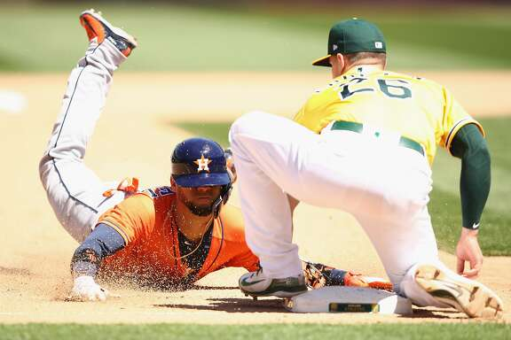 OAKLAND, CA - MAY 09:  Yuli Gurriel #10 of the Houston Astros is tagged out by Matt Chapman #26 of the Oakland Athletics as he attempted to steal third base in the eighth inning at Oakland Alameda Coliseum on May 9, 2018 in Oakland, California.  (Photo by Ezra Shaw/Getty Images)