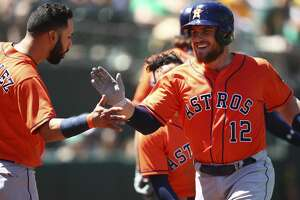 Houston Astros' Max Stassi, right, celebrates with Marwin Gonzalez (9) after hitting a home run off Oakland Athletics' Daniel Mengden during the seventh inning of a baseball game Wednesday, May 9, 2018, in Oakland, Calif. (AP Photo/Ben Margot)