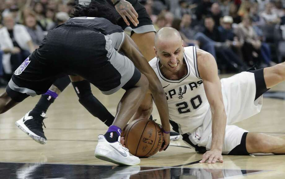 Sacramento Kings guard De'Aaron Fox, left, and San Antonio Spurs guard Manu Ginobili (20) scramble for a loose ball during the first half of an NBA basketball game, Monday, April 9, 2018, in San Antonio. (AP Photo/Eric Gay) Photo: Eric Gay, STF / Associated Press / Copyright 2018 The Associated Press. All rights reserved.