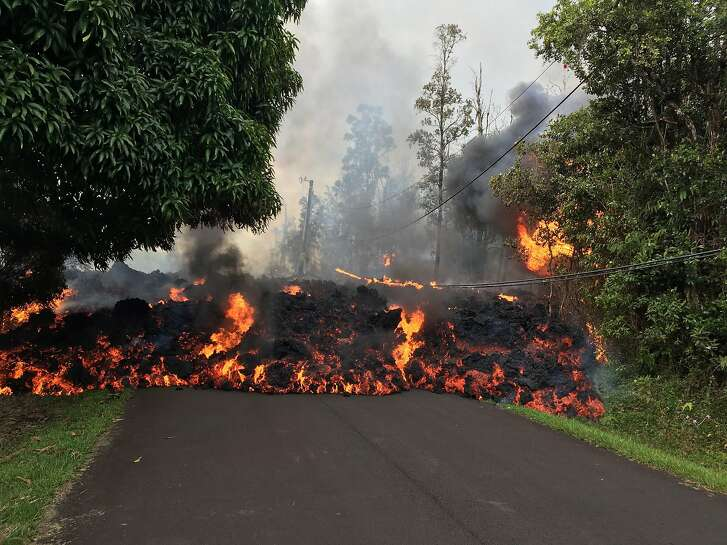 """This image obtained May 9, 2018, released by the US Geological Survey shows a lava flow moving on Makamae Street in Leilani Estates at 09:32 am local time, on May 6, 2018 in Leilani Estates, Hawaii. The Kilauea Volcano, the most active in Hawaii, was highly unstable on May 6, 2018, as lava spouted into the air and fissures emitted deadly gases -- hazards that have forced thousands of people to evacuate. / AFP PHOTO / US Geological Survey / HO / RESTRICTED TO EDITORIAL USE - MANDATORY CREDIT """"AFP PHOTO / US Geological Survey/HO"""" - NO MARKETING NO ADVERTISING CAMPAIGNS - DISTRIBUTED AS A SERVICE TO CLIENTS  HO/AFP/Getty Images"""