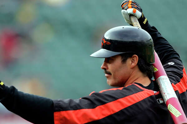 FILE - In this Aug. 15, 2005, file photo, Baltimore Orioles' Rafael Palmeiro waves to fans as he prepares to take batting practice for the team's baseball game against the Oakland Athletics in Oakland, Calif. Palmeiro says he has agreed to play with his son for the independent Cleburne (Texas) Railroaders at age 53. Palmeiro told the Dallas Morning News in a text Tuesday that he is looking forward to joining the second-year American Association team and will be teammates with his 28-year-old son Patrick. Nobody gave me a chance to go to spring training, so I will just take this path, Palmeiro said in the text. (AP Photo/Marcio Jose Sanchez, File)