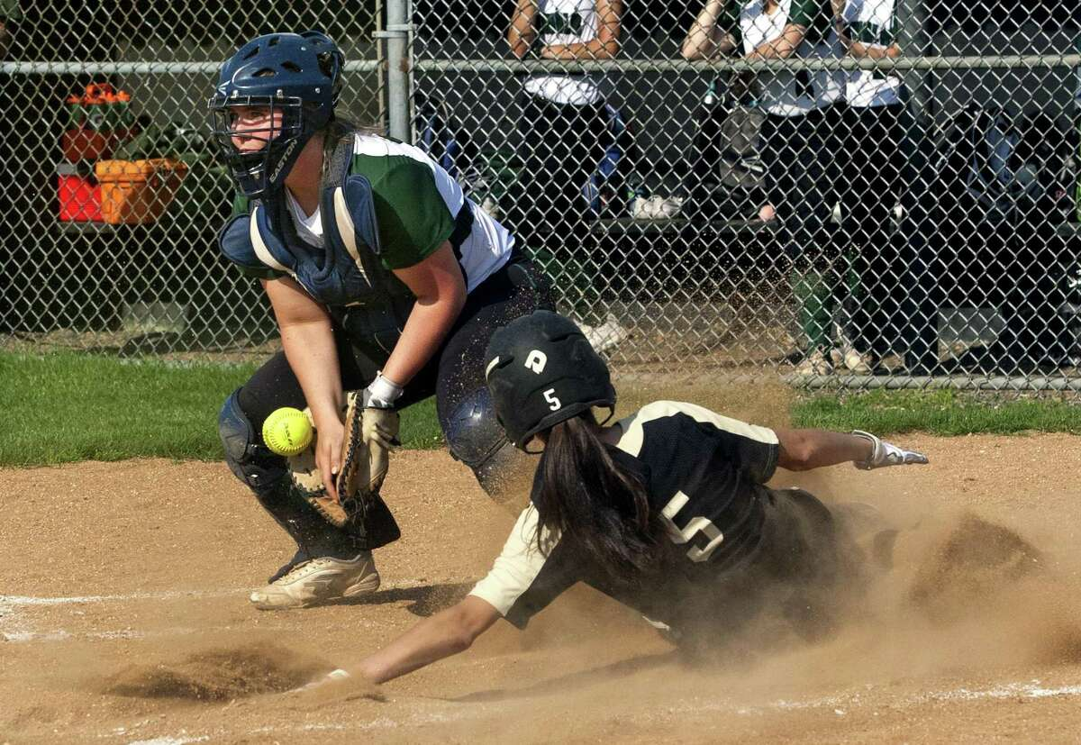 Trumbull's Julia Huzi (5) slides into home plate to score as Norwalk's Dina DiBlasio (12) bobbles the ball during softball action in Trumbull, Conn., on Wednesday May 9, 2018.