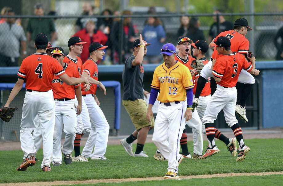 Westhill coach D.J. Mulvany walks back to his dugout as Stamford celebrates at the end of the fourth inning of an inner city rival boys baseball game played at Cubeta Field on May 8, 2018 in Stamford, Connecticut. Photo: Matthew Brown / Hearst Connecticut Media / Stamford Advocate
