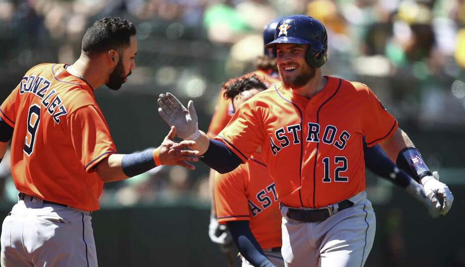 Max Stassi (12) is welcomed home by Marwin Gonzalez after tying Wednesday's game at 1 with a seventh-inning home run off Daniel Mengden. Photo: Ben Margot, STF / Associated Press / Copyright 2018 The Associated Press. All rights reserved.