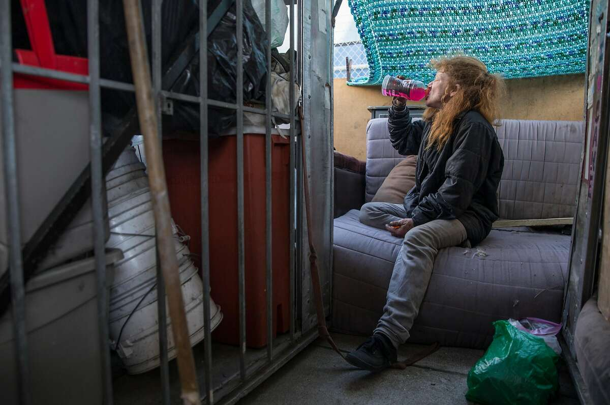 Tiger, a homeless woman, drinks Gatorade inside her structured shack at their encampment near Pennsylvania Avenue and Cesar Chavez Wednesday, May 9, 2018 in San Francisco, Calif.