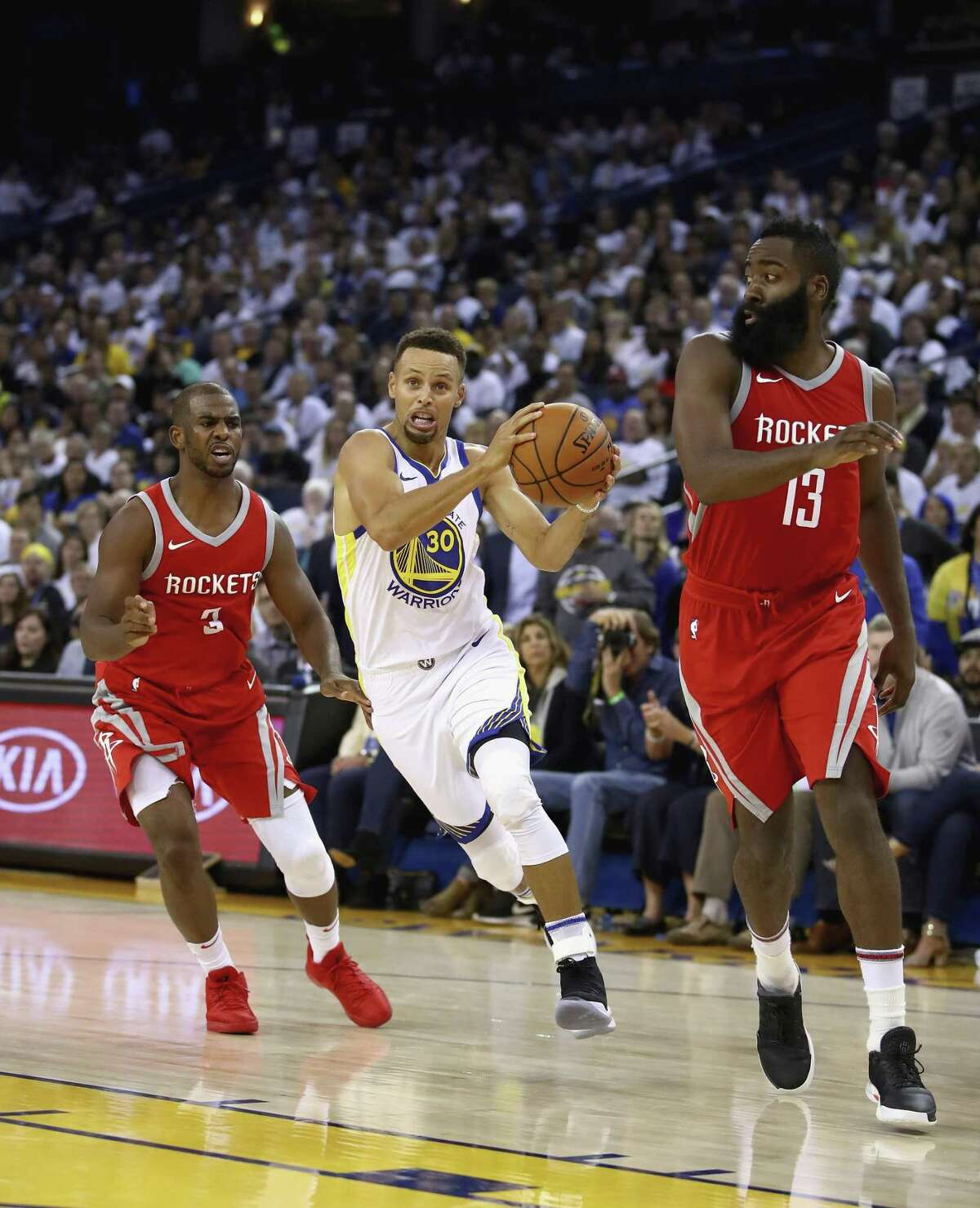 Stephen Curry drives past the Rockets' Chris Paul (left) and James Harden. Paul was acquired in a blockbuster off-season trade.