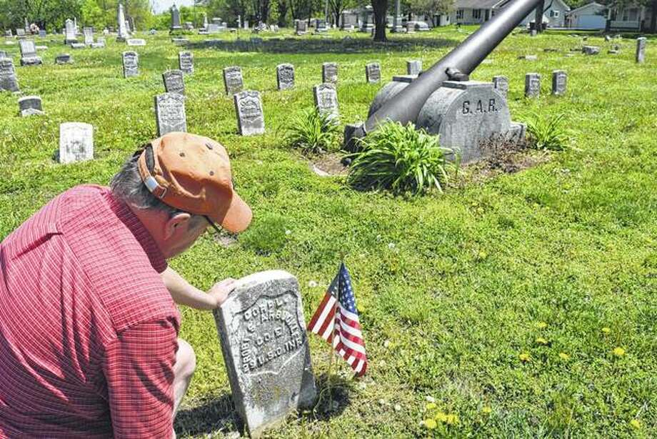 Chuck Murphy of Springfield looks at the gravestone of Robert Arbuckle, an African-American soldier who served in the Civil War and is buried in Jacksonville East Cemetery. Arbuckle will be the subject of presentations to be given on Memorial Day weekend. Photo:       Greg Olson | Journal-Courier