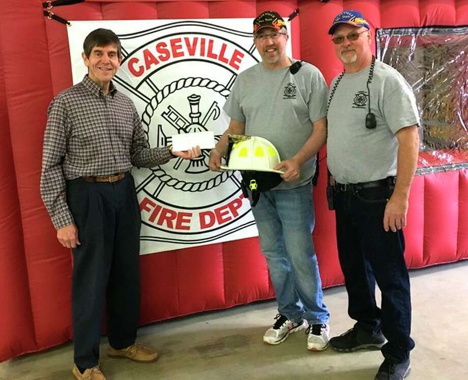 (Left) Dave Meyerrecently presented a check for $5,000 on behalf of the employees and volunteers of the Helping Hands Thrift Shop, of Caseville, along with the Caseville United Methodist Church, to Assistant Fire Chief Carl Brunni and Fire Chief Ben Willenberg, of the Caseville Fire Department. Themoney will be used toward the purchase of new helmets for the fire department. (Submitted Photo)