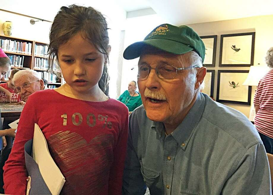 Residents at Covenant Village recently hosted second-grade students from Edna C. Stevens Elementary School in Cromwell. Here, Alan McLean enjoys the girl's pocket poem. Photo: Contributed Photo