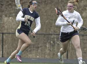 Notre Dame's Katie Ciufo (16) brings the ball upfield while being guarded by  Immaculate's Brianna Sullivan (1) during the girls high school lacrosse game between Notre Dame-Fairfield and Immaculate high schools, on Friday afternoon, April 10, 2015, played at Immaculate High School, in Danbury, Conn.