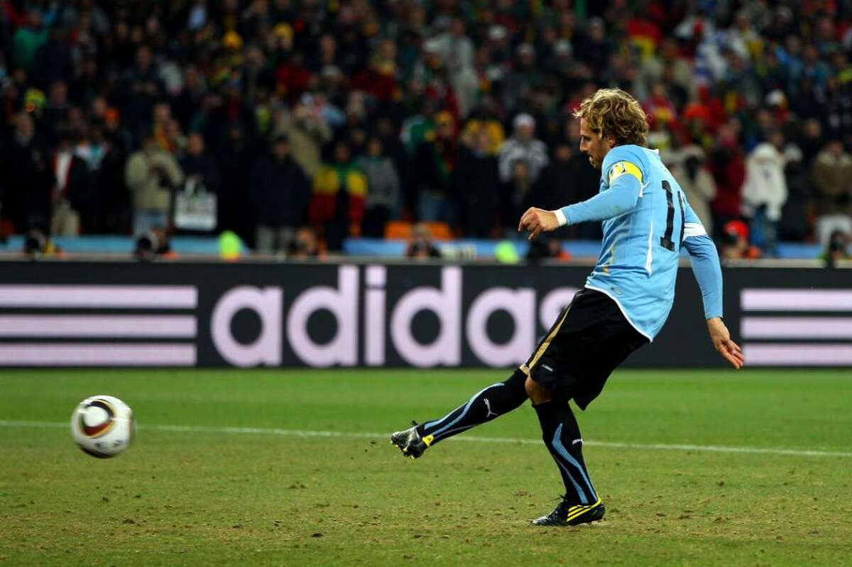 JOHANNESBURG, SOUTH AFRICA - JULY 02: Diego Forlan of Uruguay scores the first penalty in a penalty shoot out during the 2010 FIFA World Cup South Africa Quarter Final match between Uruguay and Ghana at the Soccer City stadium on July 2, 2010 in Johannesburg, South Africa. (Photo by Michael Steele/Getty Images) *** Local Caption *** Diego Forlan