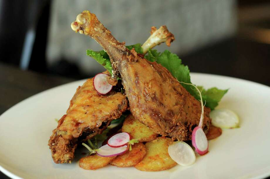 Crispy Fried Duck Legs with pomegranate-molasses-ginger glaze, chili potatoes, and watercress and radish salad at Poitin. Photo: Dave Rossman, For The Chronicle / 2018 Dave Rossman