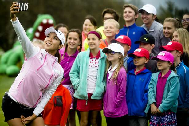 LPGA golfer Jenny Shin takes a selfie with a group of children after helping them work on their form during a clinic on Thursday, May 10, 2018 at the Midland Country Club before the announcement of a professional LPGA tournament which will take place in Midland next summer. (Katy Kildee/kkildee@mdn.net)