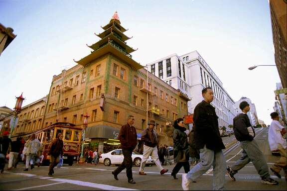 FILE--The Sing Fat Co. building, topped by an ornamental corner pagoda dominates this intersection at California and Grant Streets in San Francisco's Chinatown in this Dec. 1997 file photo. The building with its distinct pseudo-Chinese shape was designed to draw tourists.  The building was was one of the first constructed in Chinatown after the 1906 earthquake and helped create a new shopping mecca. (AP Photo/Julie Stupsker,File)