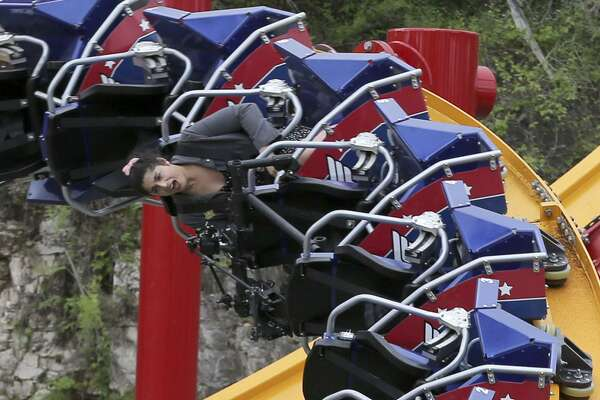 San Antonio Express-News Journalist Polly Anna Rocha (rear) rides Six Flag Fiesta Texas' new roller coaster the Wonder Woman Golden Lasso Thursday. Seats on the ride straddle a 15 ½-inch rail and the coaster was designed by Alan Schilke of Rocky Mountain Construction.