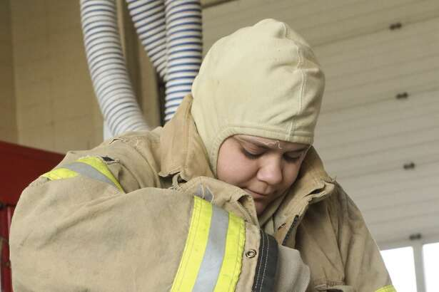 Firefighter Laura Ochoa suits out in her bunker gear March 26 at Midland Fire Department Station 3.