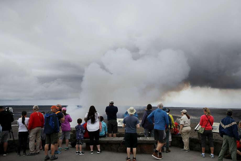 Visitors watch as steam and gas rise from Kilauea's summit crater in Volcanoes National Park, Hawaii, on Wednesday. Geologists warn that Kilauea could erupt explosively and send boulders, rocks and ash into the air around its summit in the coming weeks. Photo: Jae C. Hong / Associated Press