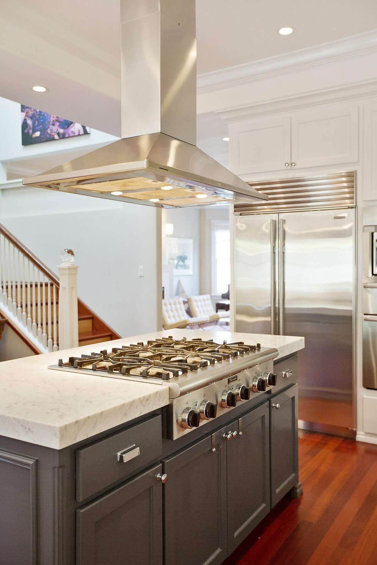 The kitchen revolves around an island with a built-in cooktop.