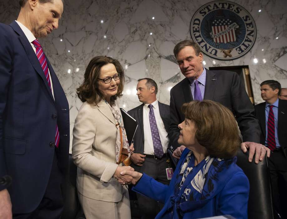At her confirmation hearing Wednesday, Gina Haspel (standing) shakes hands with Sen. Dianne Feinstein as Sens. Ron Wyden, D-Ore. (left) and Mark Warner, D-Va., look on. Photo: J. Scott Applewhite / Associated Press