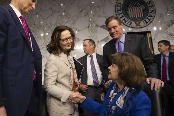 Gina Haspel, standing center, President Donald Trump's pick to lead the Central Intelligence Agency, is welcomed at her confirmation hearing before the Senate Intelligence Committee by, from left, Sen. Ron Wyden, D-Ore., Sen. Dianne Feinstein, D-Calif., seated, and Vice Chairman Mark Warner, D-Va., on Capitol Hill in Washington, Wednesday, May 9, 2018.  (AP Photo/J. Scott Applewhite)