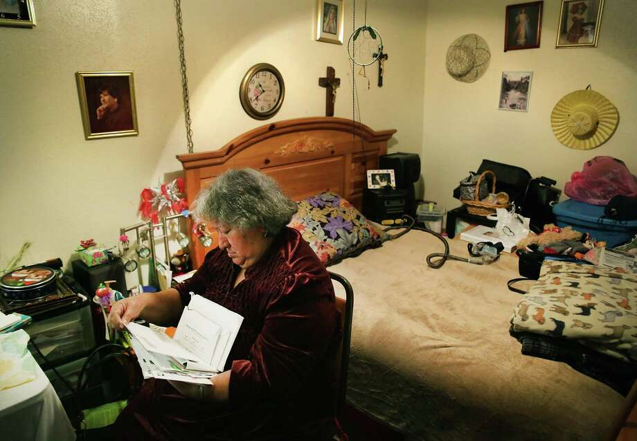 Cruz Soto, who lives in the Soap Factory Apartments, looks through her bills in her efficiency apartment. The apartment complex borders the new San Pedro Creek Culture Park. Photo: Bob Owen /San Antonio Express-News / ©2018 San Antonio Express-News