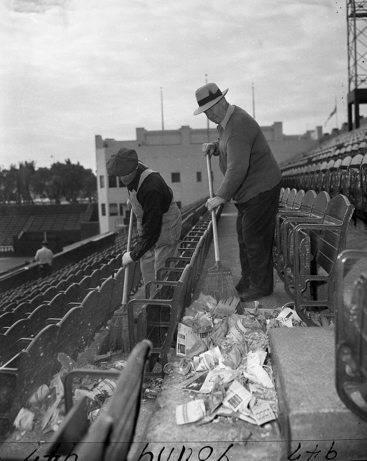Janitors clean up peanut shells after the big peanuts giveaway at San Francisco Seals opening Day April 16, 1950 at Seals Stadium,