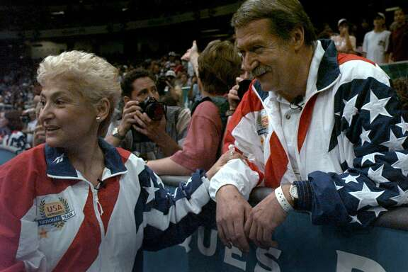 FILE - In this July 23, 2004, file photo, Martha and Bela Karolyi watch together as the U.S. womens gymnastic team celebrates winning the gold medal at the Centennial Summer Olympic Games in Atlanta. Victims of disgraced sports doctor Larry Nassar are imploring Texas authorities to investigate whether Bela and Martha Karolyi could have done more to prevent Nassar's sexual abuse at the couple's Texas training center. Five former gymnasts, including two who say Nassar abused them at the Karolyis' ranch near Huntsville, addressed reporters Thursday, May 10, 2018, outside state Attorney General Ken Paxton's office. (AP Photo/Amy Sancetta, File)
