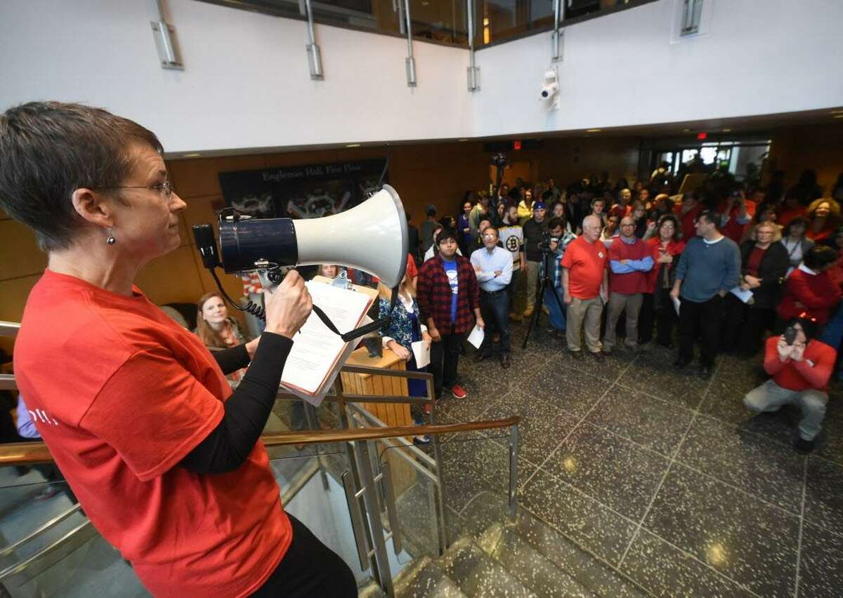 Cynthia Stretch, Southern Connecticut State University professor of English and American Literature, left, participates in a protest and rally at SCSU's Engelmann Hall Rotunda by Connecticut State University faculty and students against the Board of Regents contract proposals during negotiations and for a