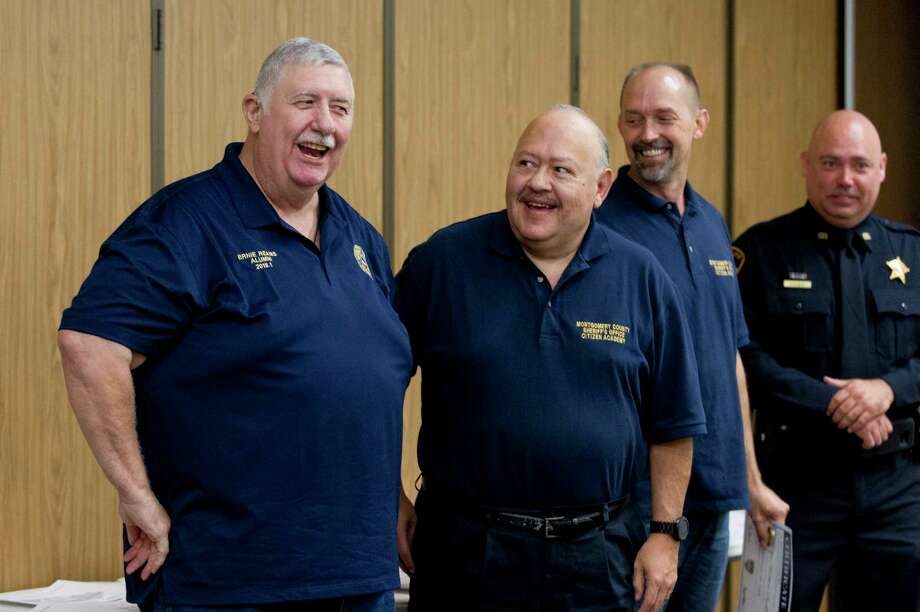 Ernie Reams, left, jokes beside Jake Gonzales as fellow academy citizens, law enforcement and medical personnel were recognized Wednesday for helping save Reams' life after his cardiac arrest during the second meeting of the citizen's academy. Photo: Jason Fochtman, Staff Photographer / © 2018 Houston Chronicle